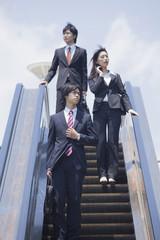 エスカレーターを降りるビジネスマンとビジネスウーマン