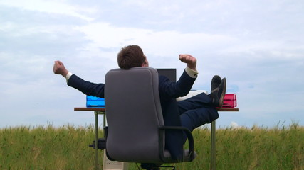 Business person taking break at office desk in a green field
