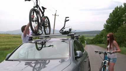 Cyclists traveling with two bikes on the roof of car