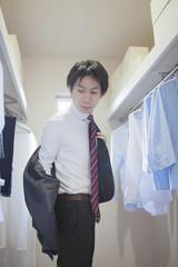 クローゼットでスーツを着る男性