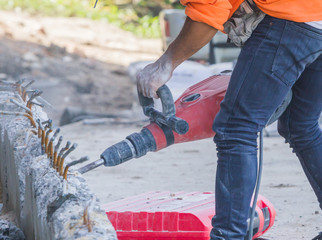 Workers use a jackhammer to break concrete.