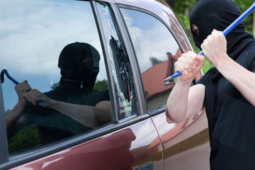 The burglar smash the glass of the car