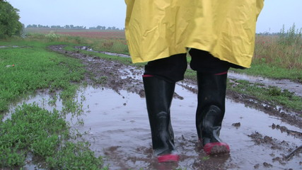 Man washes away the dirt from rubber boots in puddle
