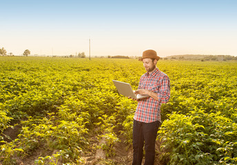 Happy farmer with laptop computer in front of field