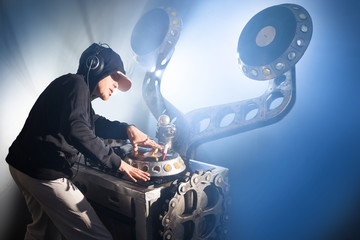 Dj man with headphones playing on vinyl in a nightclub.