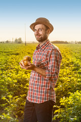 Happy farmer holding potatoes in front of field