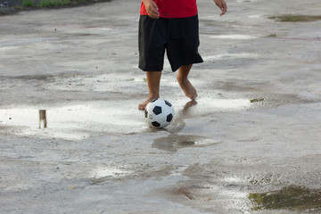 poor children playing soccer without soccer boots on concrete fl