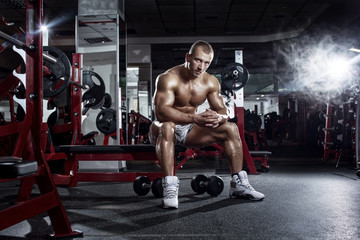 bodybuilder athletic guy relaxing after workout in gym