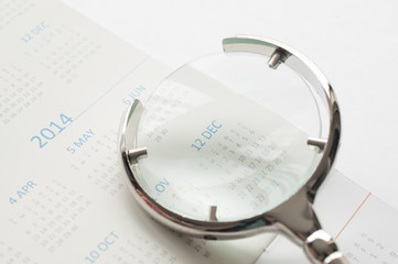 Hand holding magnifying glass to checking calendar of December