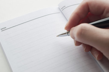 Woman's hand taking note