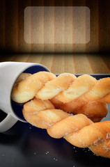 Three breads twists with glass front of wood light background
