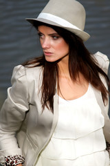Beautiful brunette young woman at see with hat on