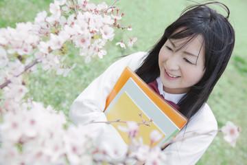 ノートを持って桜の木の下に立つ高校生