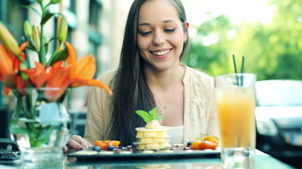 Young woman gets delicious dessert from waiter in cafe