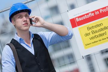 Ingenieur mit Telefon auf Baustelle