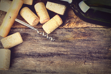 Bottle of white wine, corkscrew and corks on wooden table.