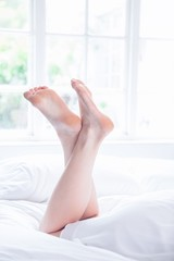 Female legs lying on bed