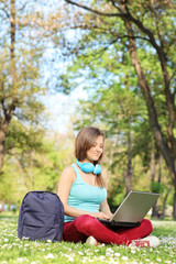 Female student studying on laptop in park
