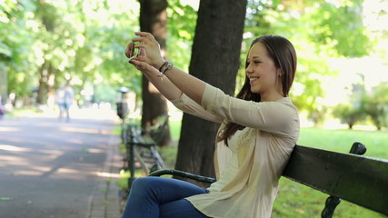 Young woman taking photo of herself with smartphone in the park