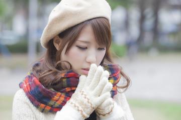 マフラーと手袋をする帽子を被った女性