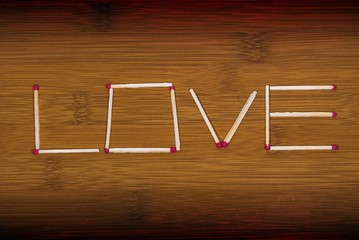 Inscription - Love on wooden background