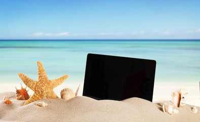 Summer beach with tablet in sand