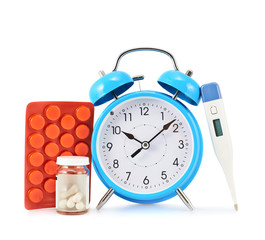 Alarm clock next to tablets and thermometer