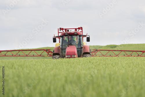 Leinwandbild Motiv Traktor und Pestizide im Getreidefeld