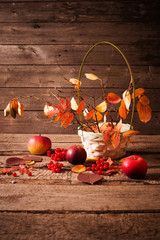 autumn leaves and apples on wooden background
