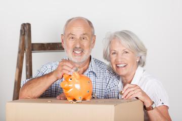 lachendes älteres paar spart geld beim umzug