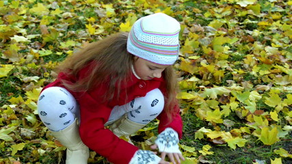 Little girl in a red coat collects fallen autumn leaves
