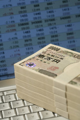 Bundles of 10 000 yen notes on a computer keyboard