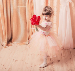 Adorable little girl dressed as a ballerina in a tutu indoor