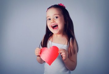 Cute little girl with long hair playing with a red heart