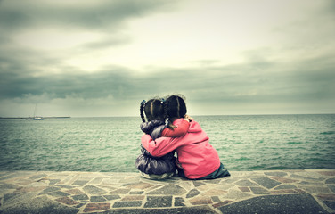 Two little girls sitting near the sea