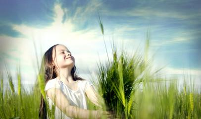 Little happy girl on wheat field