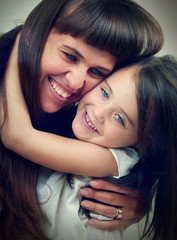 Little cute girl hugging her mother with long hair