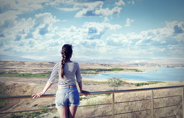 Young woman looking at a beautiful view of the lake and mountain