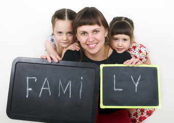 Little cute girls with mom hold a board with the word Family