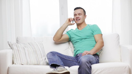 man with smartphone sitting on couch at home