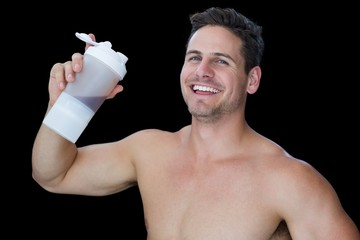 Happy muscular man holding protein drink