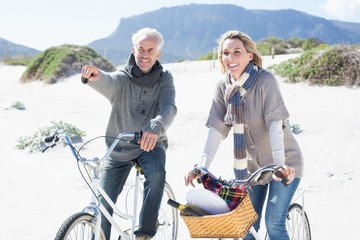 Carefree couple going on a bike ride and picnic on the beach