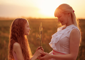 mother and daughter holding spikelets at sunset