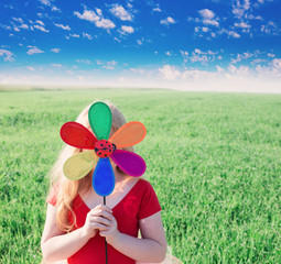 girl holding a toy flower on background grass and sky