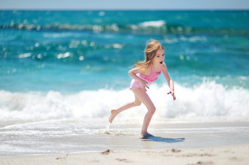 Cute little girl playing on a beach