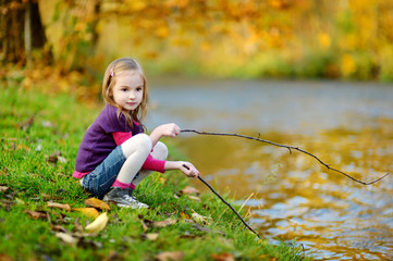 Adorable girl playing by a river on autumn day