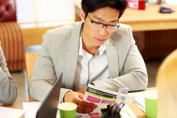 Asian businessman in glasses sitting at the table