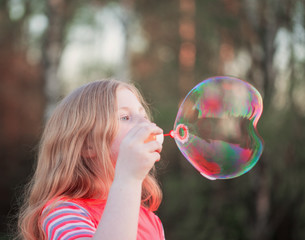 girl blowing soap bubbles outdoor