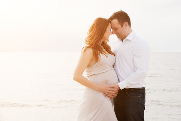 A pregnant woman with her husband on the beach