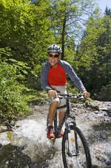 Mountainbiker fährt durchs Wasser